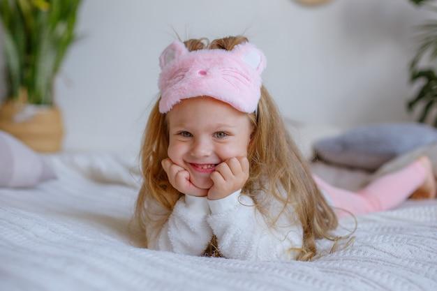 Bambina in pigiama sdraiato sul letto