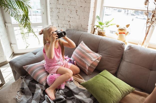 Bambina che gioca in una camera da letto in stile pigiama carino e comfort per scattare una foto divertendosi