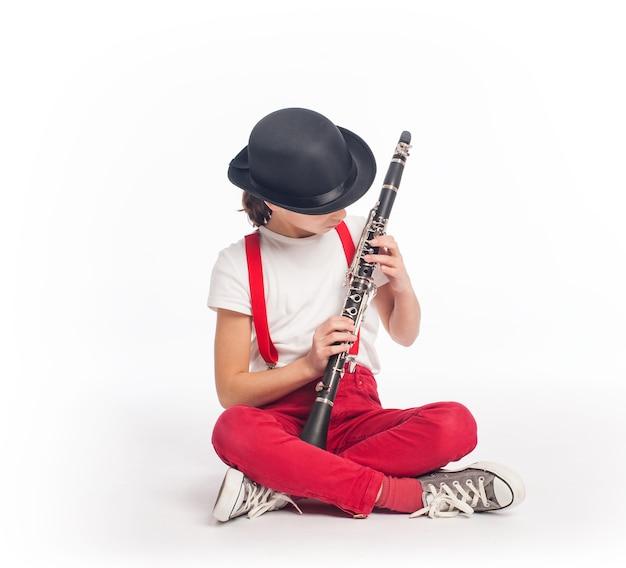 Bambina che gioca clarinetto su uno sfondo bianco