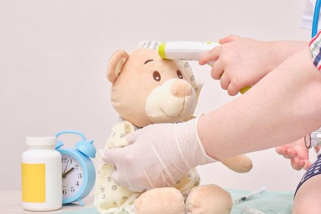 Bambina che gioca medico. un bambino con uno stetoscopio misura la temperatura di un orsacchiotto con un termometro a infrarossi senza contatto