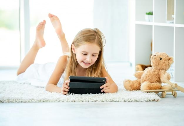 Bambina che gioca sul suo tablet
