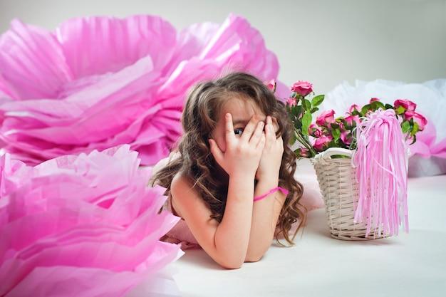 Bambina che gioca a nascondino vicino a enormi fiori di carta
