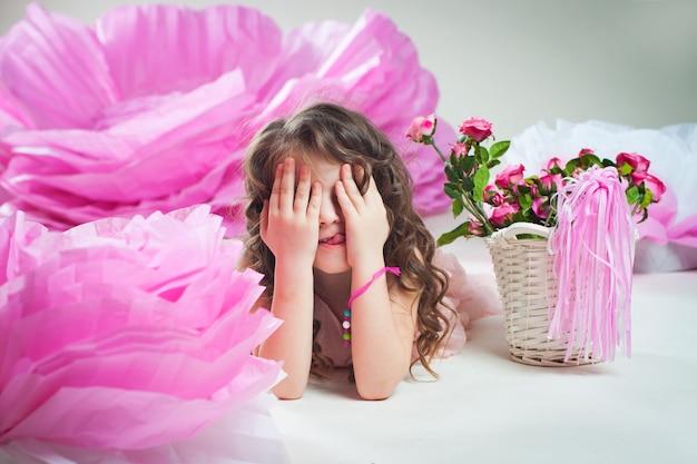 Bambina che gioca a nascondino vicino a fiori enormi