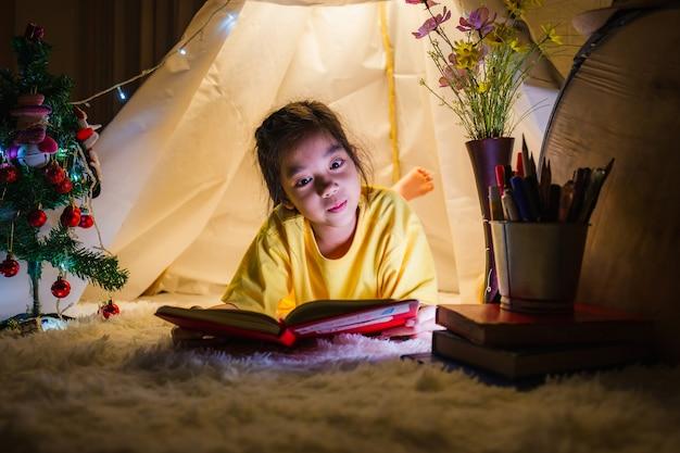 Bambina che gioca leggendo un libro in tenda, bambino che gioca in casa