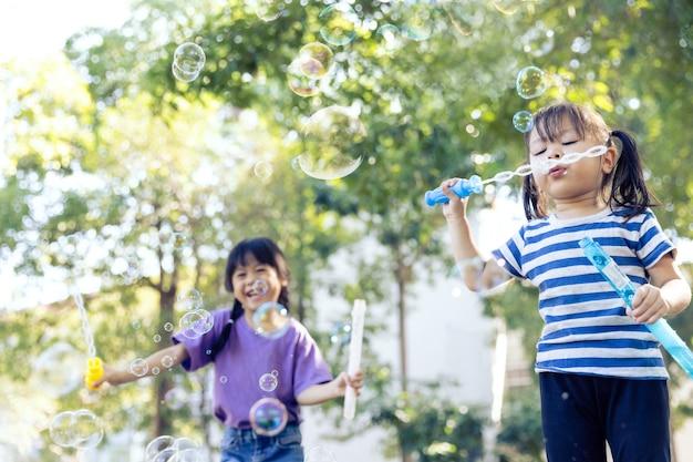 Bambina che gioca bolla di sapone nel parco giochi.