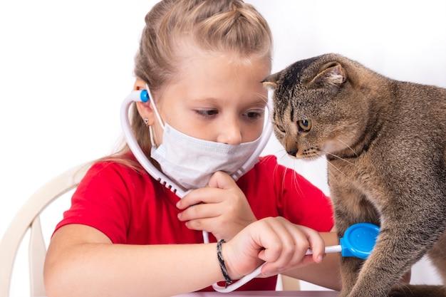 Bambina che gioca al veterinario - consultando il suo piccolo gattino.