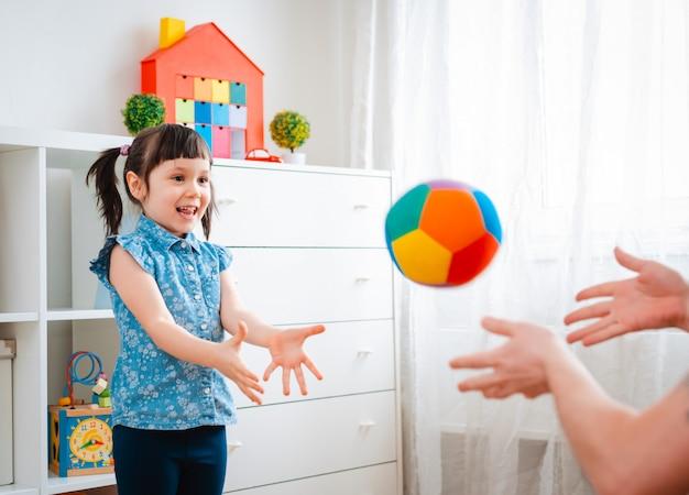 Bambina che gioca con una palla nella stanza dei giochi.