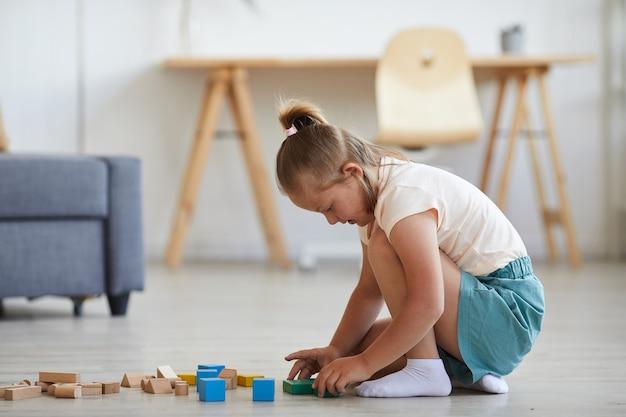 Bambina che gioca con i blocchi mentre è seduto sul pavimento nel soggiorno di casa