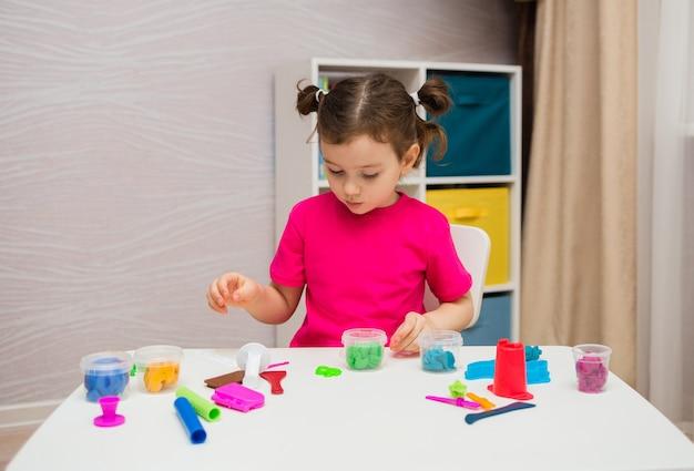 Bambina che gioca con la plastilina al tavolo in camera
