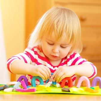 Bambina che gioca con la plastilina