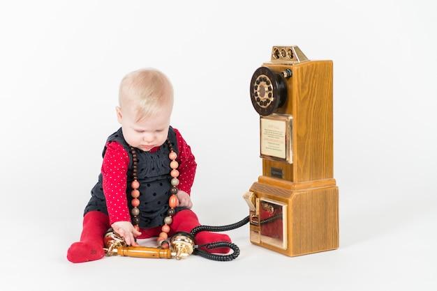 Bambina che gioca con un telefono vintage