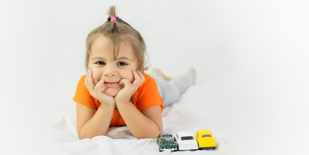 Bambina che gioca con la macchinina bianca. sdraiato sul lenzuolo bianco. sorridente.