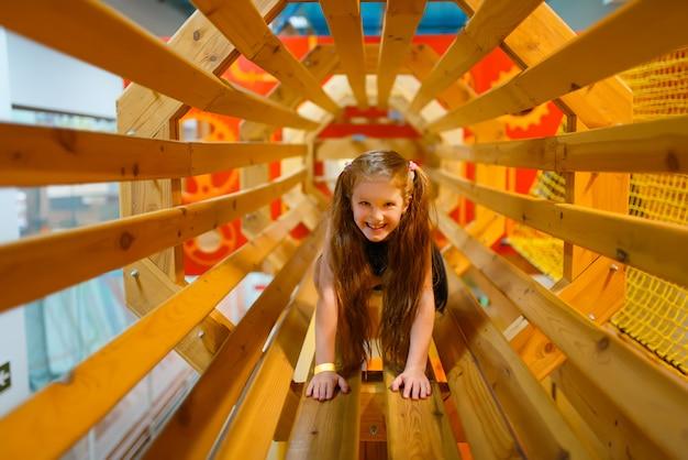Bambina che gioca nel labirinto di legno, parco giochi nel centro di intrattenimento. area giochi interna, sala giochi