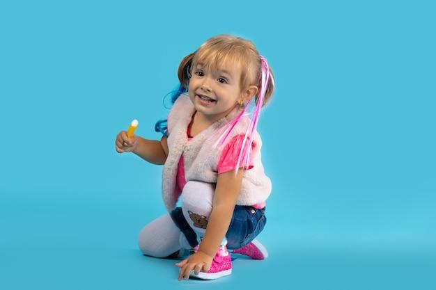 La bambina gioca sul pavimento e mangia i dolci. foto su una parete blu. concetto di vacanza, halloween.