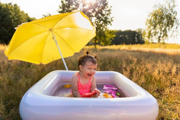 La bambina gioca nello stagno gonfiabile.