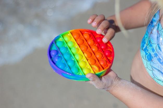 Una bambina gioca un popolare giocattolo antistress colorato in silicone sulla spiaggia semplice fossetta