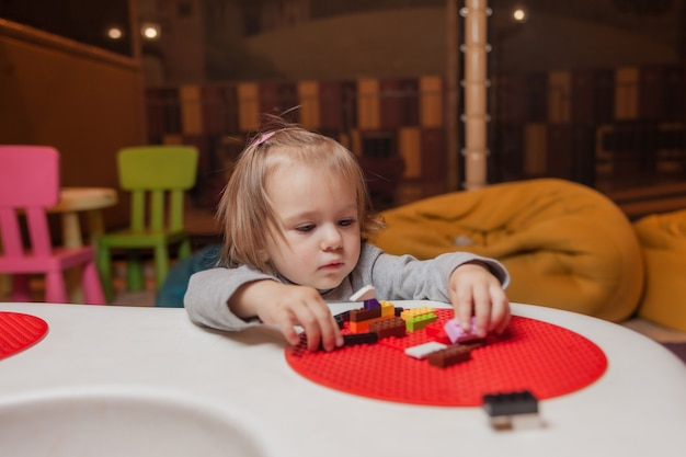 La bambina gioca i mattoni del giocattolo al tavolo nel centro di intrattenimento per bambini