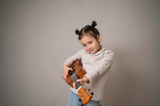 La bambina gioca lo sviluppo creativo dell'ukulele nell'educazione musicale dei bambini fin dall'infanzia insegnando musica online a casa