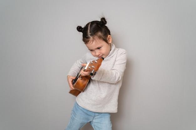 La bambina suona l'ukulele.