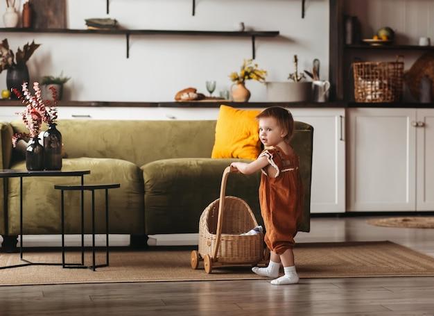 Una bambina gioca con le bambole e una carrozzina. la stanza dei bambini. infanzia felice