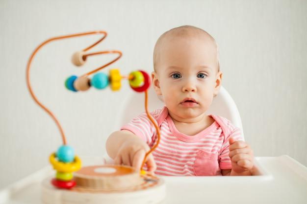 Bambina gioca con un labirinto educativo giocattolo.