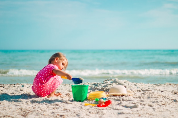 Una bambina gioca con una scapola e un secchio sulla spiaggia con un vestito rosa a cuore