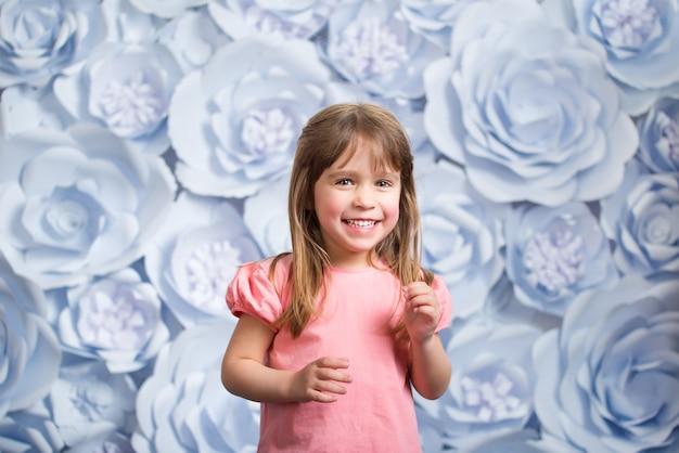 Ritratto di bambina su un muro di fiori di carta