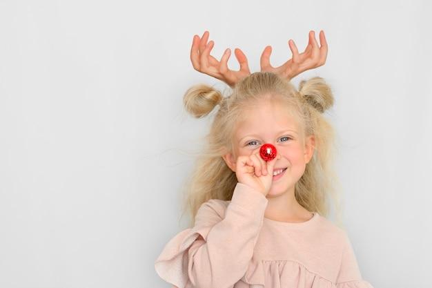Ritratto di bambina con naso rosso e corna di cervo fatte di mani