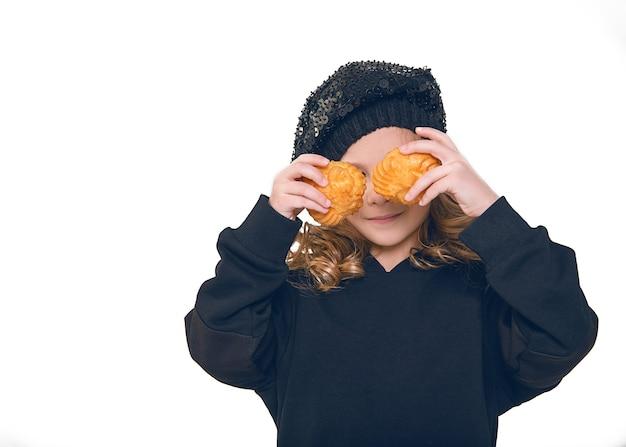 Bambina in posa su sfondo bianco in studio con due biscotti nelle sue mani, si concede, chiudendo gli occhi. concetto di bambini e cottura. avvicinamento