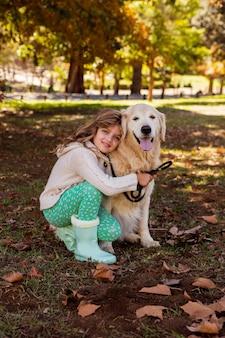 Bambina che propone con il suo cane