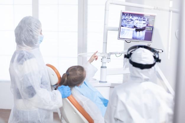Bambina in tuta dpi che punta alla radiografia digitale durante la consultazione. stomatolog in tuta protettiva per coroanvirus come precauzione di sicurezza guardando la radiografia digitale dei denti da bambino durante la consultazione.