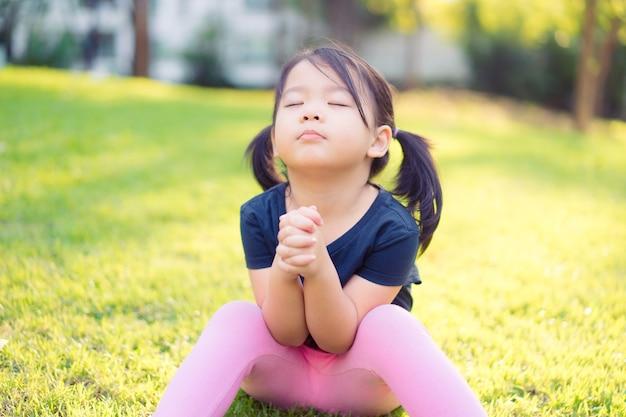 Bambina che prega al mattino al parco.