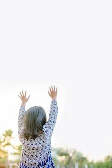 Bambina che prega e alza le mani per adorare dio
