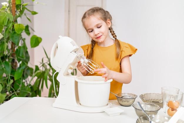 La bambina prepara l'impasto o la crema in un mixer sommergibile.