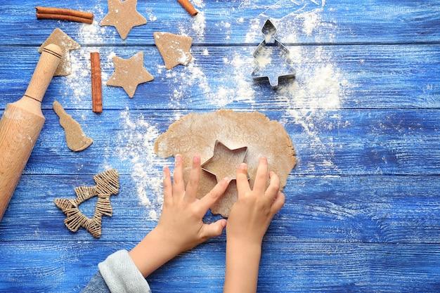 Bambina che prepara i biscotti di natale a tavola