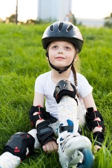 Bambina in dispositivi di protezione e rulli. seduto sull'erba un parco. giovane pattinatore felice