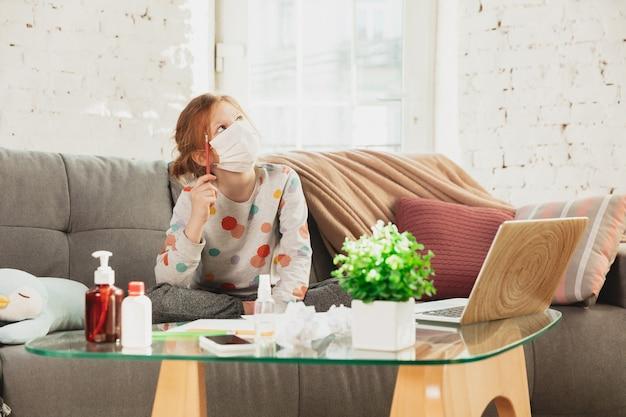 Bambina in maschera protettiva isolata a casa con sintomi respiratori del coronavirus come febbre, mal di testa, tosse in condizioni lievi. sanità, medicina, quarantena, concetto di trattamento. si sente male.