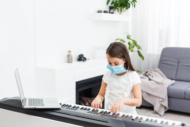 Bambina in maschera protettiva che impara il pianoforte durante la quarantena. concetto di coronavirus.