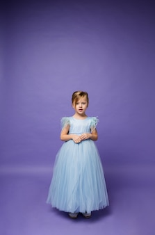 Una bambina in un gonfio vestito blu da principessa sta sulla viola