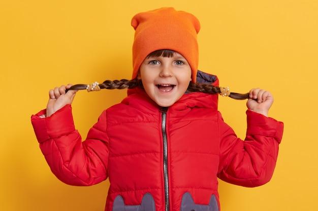 La bambina che tira le sue trecce ai lati, guardando davanti con l'espressione facciale eccitata, tiene la bocca aperta, indossa abiti caldi, in piedi isolato sopra il muro giallo