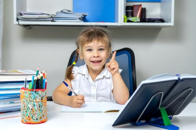 Pupilla bambina che fa i compiti e alza il dito dimostrando una grande idea