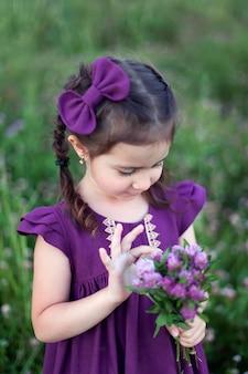 Una bambina in un vestito viola si trova in un campo di fiori e tiene un bouquet