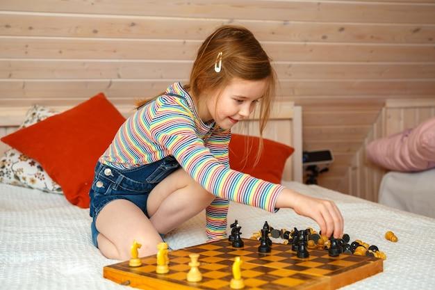 La bambina mette i pezzi su una scacchiera. partita a scacchi