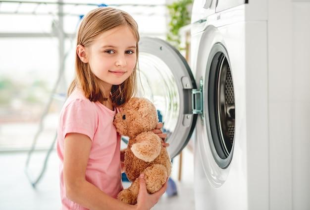 Bambina che mette peluche in lavatrice aperta e sorridente