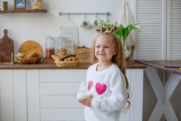 Bambina in pigiama in cucina a bere il latte
