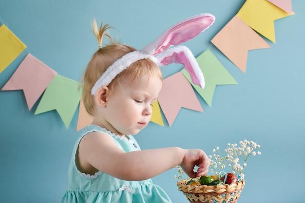 Una bambina in orecchie di coniglio prende le uova da un canestro