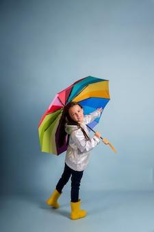 Una bambina con un impermeabile e stivali di gomma gialli tiene un ombrello multicolore su uno sfondo blu con una copia dello spazio