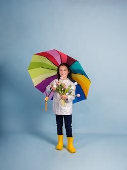Una bambina con un impermeabile e stivali di gomma gialli tiene un ombrello multicolore e un mazzo di tulipani su uno sfondo blu