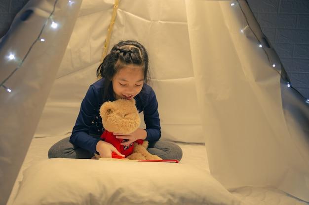Bambina che legge un libro in tenda, bambino adorabile divertente divertendosi nella stanza dei bambini.