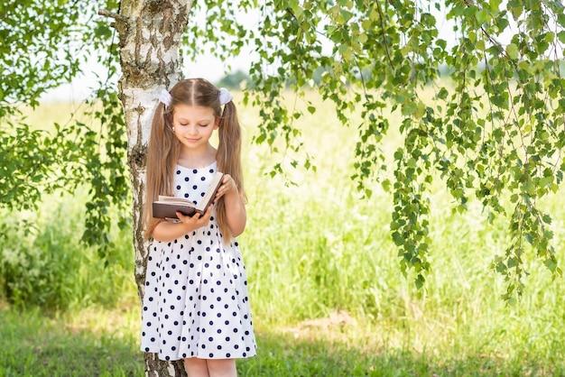 Una bambina legge un libro in una soleggiata giornata estiva sotto un albero.